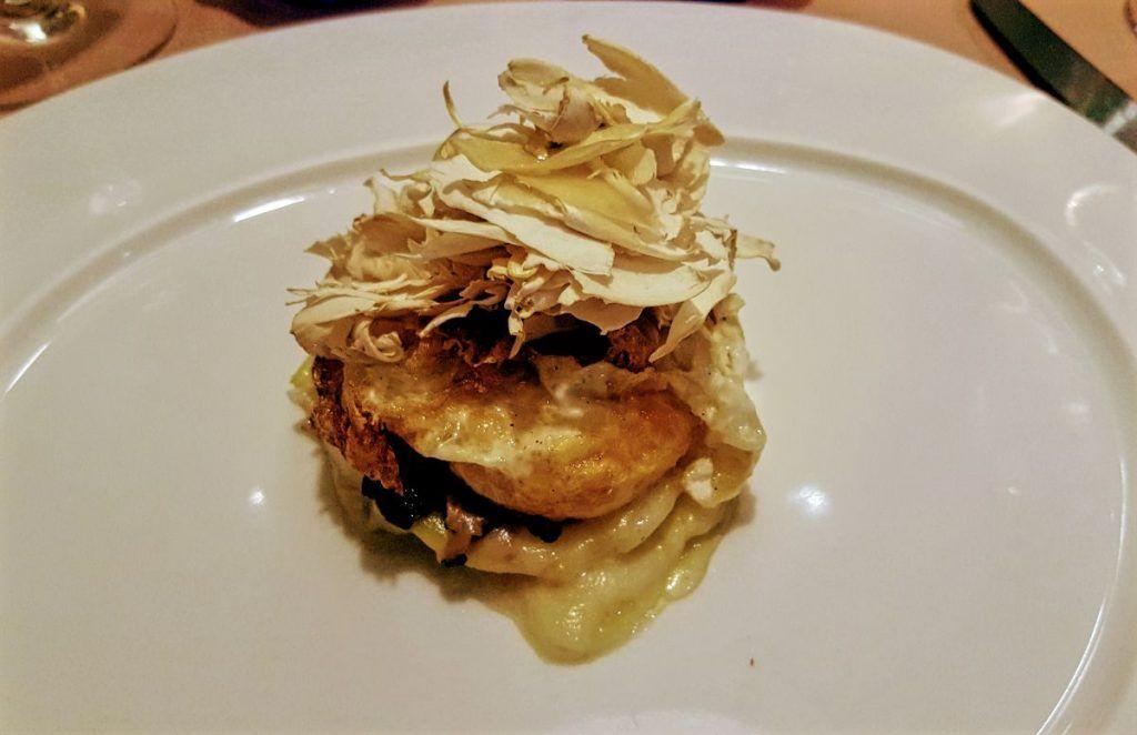 Ars Vivendi Huevo frito sobre timbal de patatas, queso ahumado, trufa y foie de pato, coronada con finas láminas de setas frescas de temporada